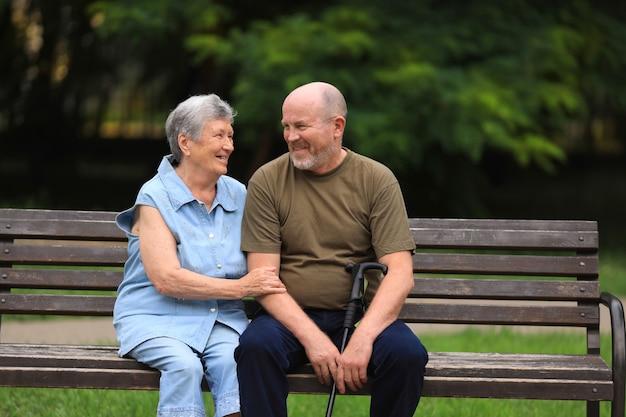 Felice l'uomo anziano e la donna disabile si siedono sulla panchina all'aperto nel parco estivo