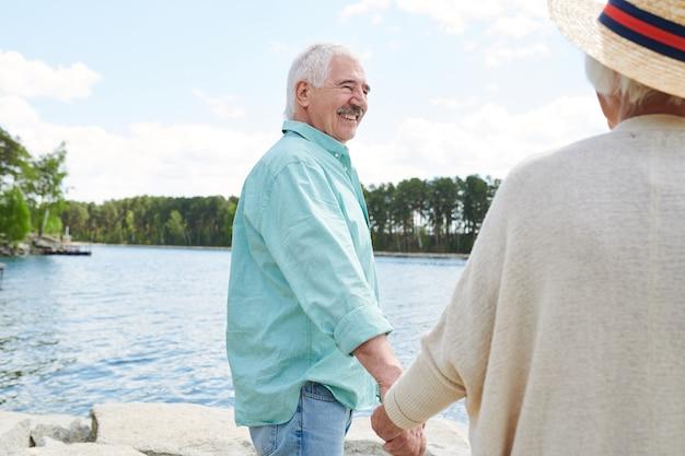 Felice l'uomo anziano in abbigliamento casual che tiene la moglie per mano mentre entrambi trascorrono il fine settimana in riva al lago nel paese