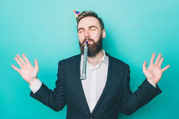 Felice l'uomo è in piedi e godersi il momento indossando un cappello da festa