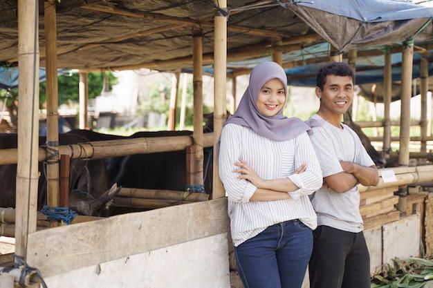 Felice l'uomo e la donna in piedi nella fattoria. eid adha sacrificio concetto