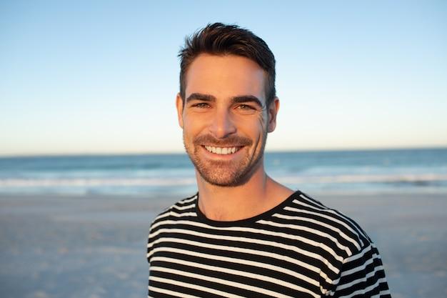 Felice l'uomo in piedi sulla spiaggia