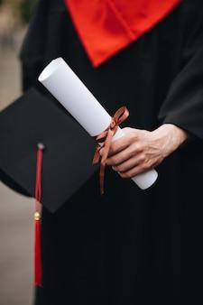 Felice laureato in abito regge un diploma di laurea