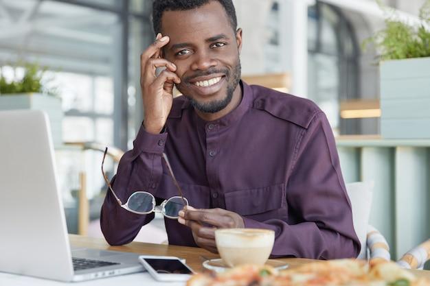 Felice libero professionista maschio dalla pelle scura utilizza moderni gadget elettronici per il lavoro a distanza, si siede contro l'interno accogliente della caffetteria, beve caffè espresso aromatico