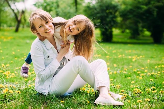 Felice madre e figlia nel parco sul prato verde