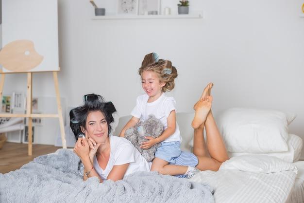 Felice madre e figlia piccola in bigodini. felice mamma e figlia divertirsi sul letto in pigiama. famiglia amorevole in camera da letto in stile scandinavo.