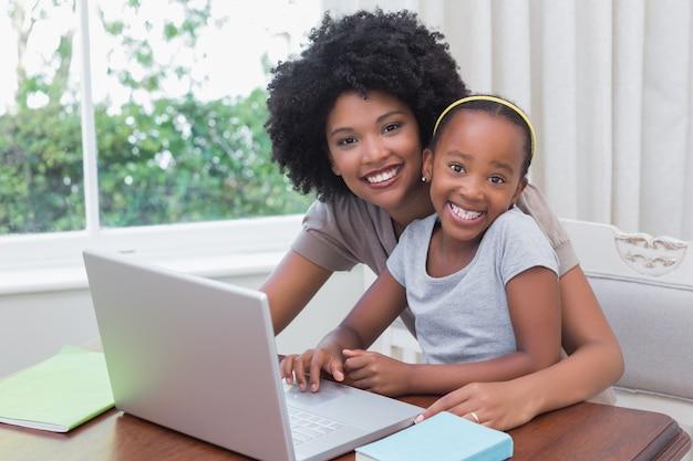Felice madre e figlia usando il portatile