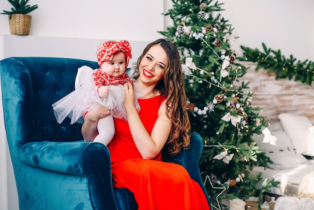 Felice madre in abito rosso con la sua piccola figlia in abito seduto sulla sedia in sala vacanze decorate con un elegante albero di natale
