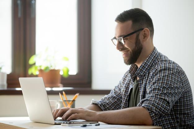 Felice maschio scrivendo posta positiva al cliente