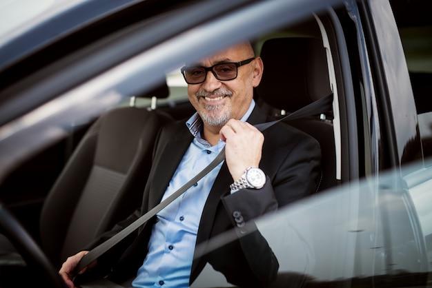 Felice maturo uomo d'affari sta allacciando la cintura di sicurezza e si prepara per guidare un'auto.