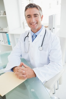 Felice medico seduto alla sua scrivania