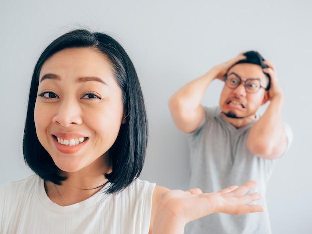 Felice moglie asiatica e marito perdente arrabbiato.