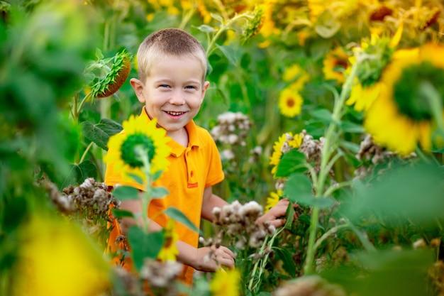 Felice neonato biondo seduto in un campo con girasoli in estate