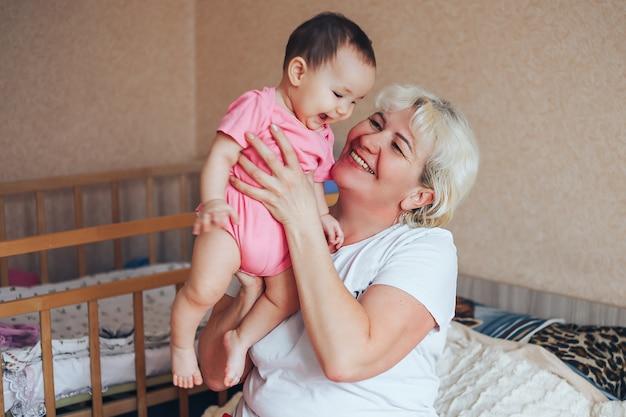 Felice nonna con nipotina che si abbracciano a casa