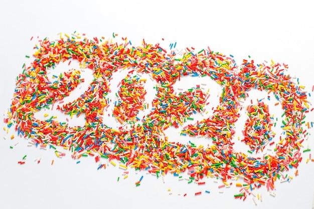Felice nuovo anno 2020. la forma variopinta di numero con lo zucchero dell'arcobaleno luminoso spruzza isolato su bianco