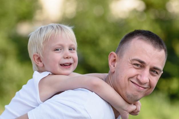 Felice padre con figlio piccolo torna all'aperto. alberi verdi sfocati in lontananza. amicizia e paternità. ritratto del primo piano