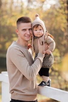 Felice padre e figlia che giocano mentre si cammina in un bellissimo parco d'autunno