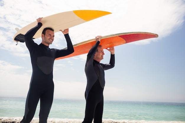 Felice padre e figlio che trasportano una tavola da surf sopra la testa