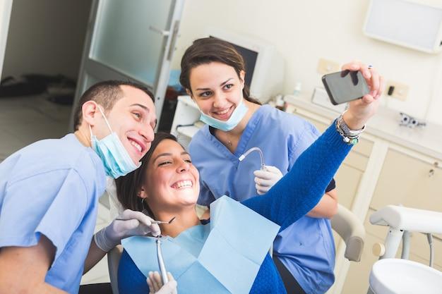 Felice paziente, dentista e assistente prendendo selfie tutti insieme