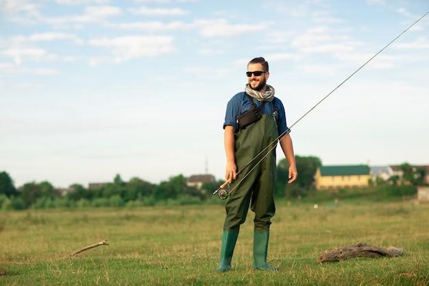 Felice pescatore con muta speciale e canna da pesca
