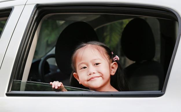 Felice piccolo bambino asiatico guardando fuori dalla finestra dell'auto.
