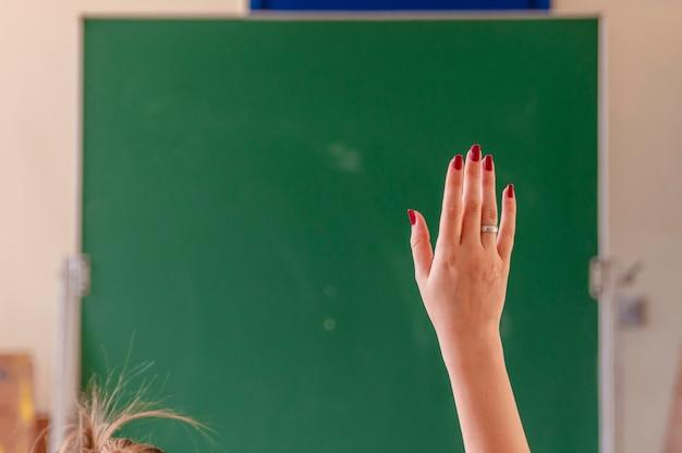 Felice ragazza alzato le mani in classe