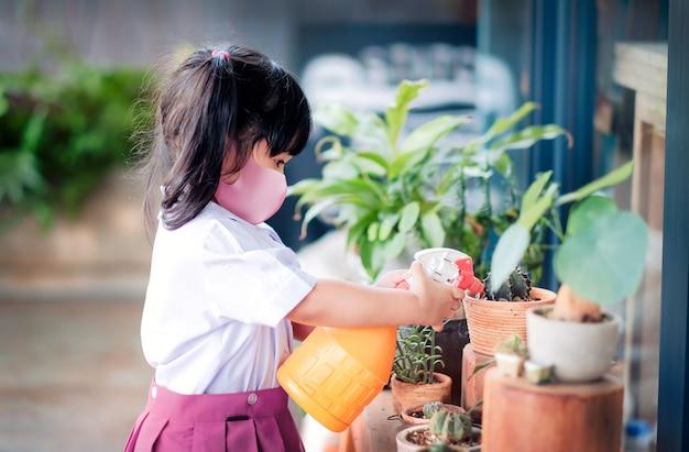 Felice ragazza asiatica che indossa una maschera di protezione chirurgica mentre si gode in giardino a scuola oa casa, un bambino in uniforme da studente sta irrigando la pianta