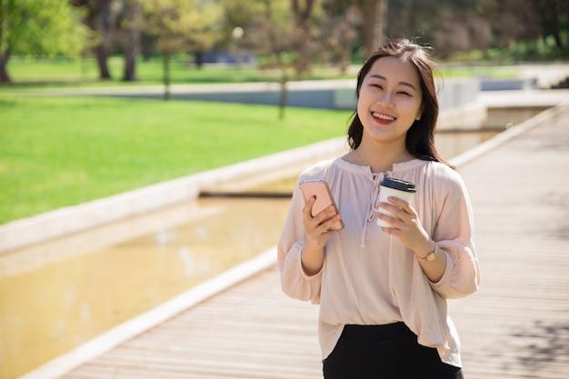 Felice ragazza asiatica gioiosa con smartphone e caffè a piedi