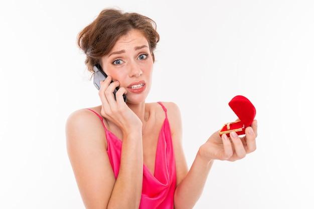Felice ragazza europea con scatola con anello di fidanzamento telefonando raccontare notizie ad un amico sul muro bianco