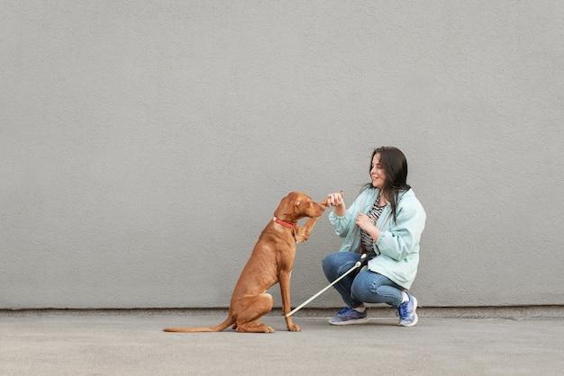Felice ragazza in abbigliamento casual addestra un cane
