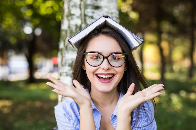 Felice ragazza seria dai capelli scuri in giacca di jeans e occhiali legge il libro contro il parco verde estivo.