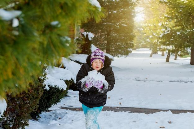 Felice ragazzino sta giocando nella neve, buon tempo invernale