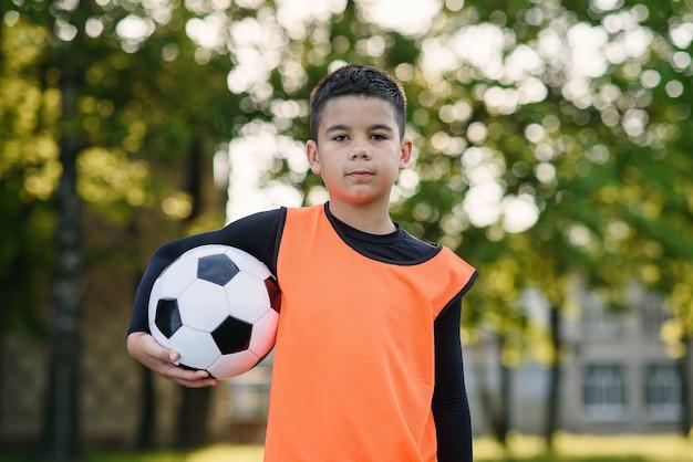 Felice ragazzo adolescente in uniforme di calcio tiene una palla dopo l'allenamento mattutino