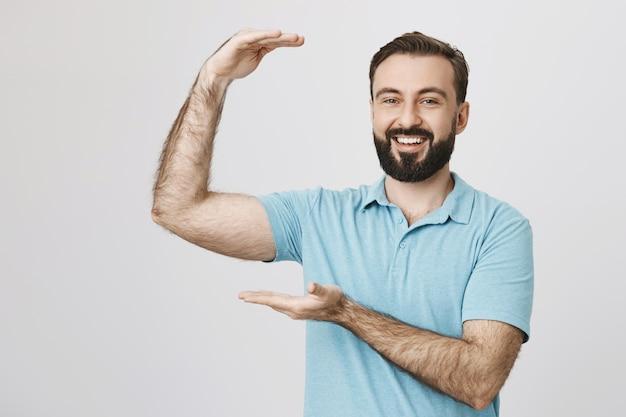 Felice ragazzo barbuto promuove un grande oggetto, qualcosa di grande