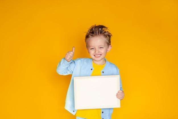 Felice ragazzo carino 5-6 anni in possesso di un foglio di carta bianco bianco in una cornice leggera.