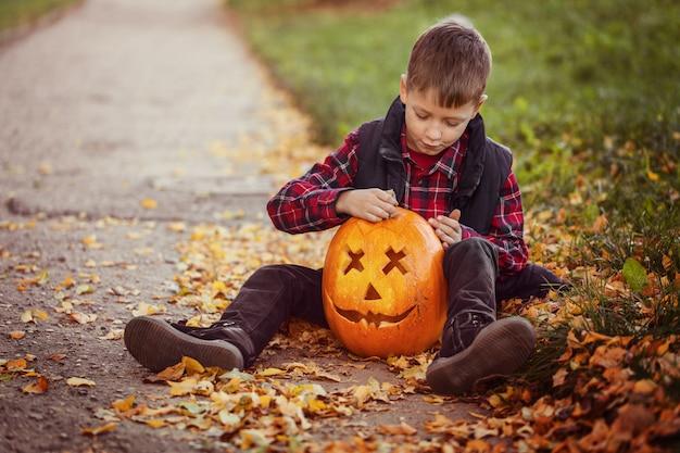Felice ragazzo carino bambino con zucca di halloween nel parco d'autunno.