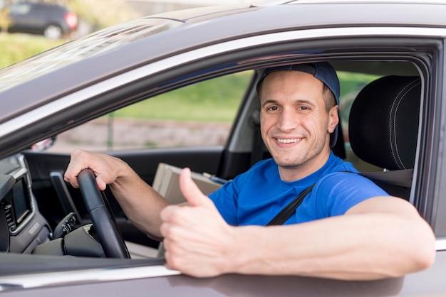 Felice ragazzo delle consegne in auto