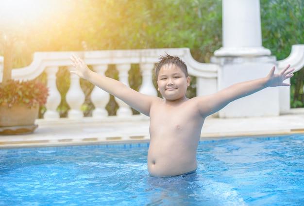 Felice ragazzo grasso obeso in piscina,