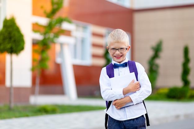 Felice ragazzo scolaro biondo con gli occhiali con uno zaino e un libro bianco si trova a scuola e ride. giorno della conoscenza