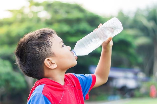 Felice ragazzo studente bambino asiatico bere un po 'd'acqua da una bottiglia di plastica. dopo aver finito dall'esercizio.