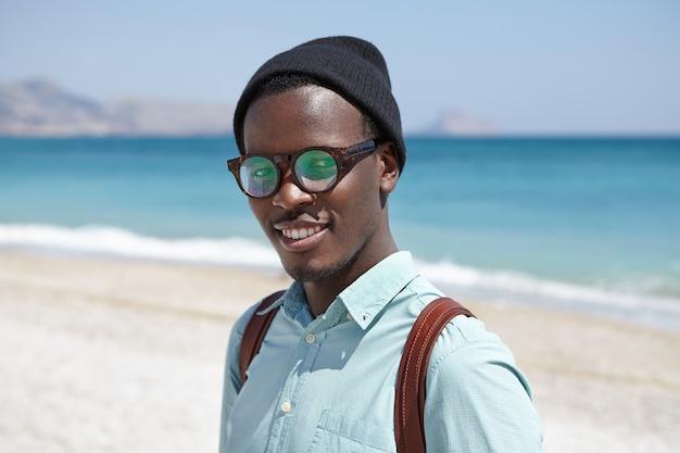 Felice rilassato giovane hipster dalla pelle scura in tonalità e copricapo in piedi contro il cielo blu chiaro e vasto oceano azzurro, trascorrendo le vacanze estive nella località turistica, guardando con un sorriso gioioso