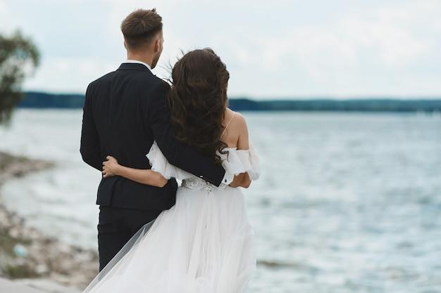 Felice romantica coppia in amore, uomini belli in abito e giovane donna in abito da sposa bianco abbraccia insieme e in posa sul litorale e guarda l'orizzonte
