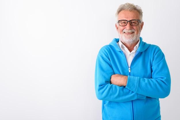 Felice senior barbuto uomo sorridente con le braccia incrociate pronto per la palestra su bianco