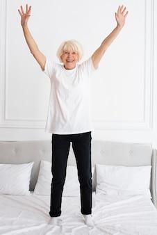Felice senior in piedi sul letto