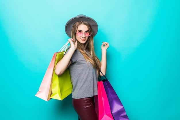 Felice shopping donna sorridente e indossa un cappello isolato su sfondo verde