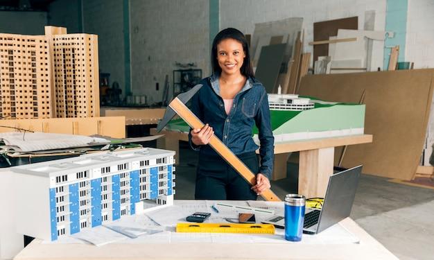 Felice signora afro-americana con la bacchetta vicino tavolo con computer portatile e modello di edificio