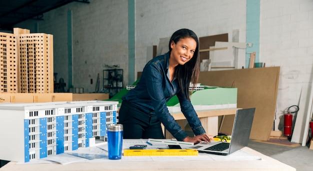 Felice signora afro-americana con laptop e modello di costruzione sul tavolo