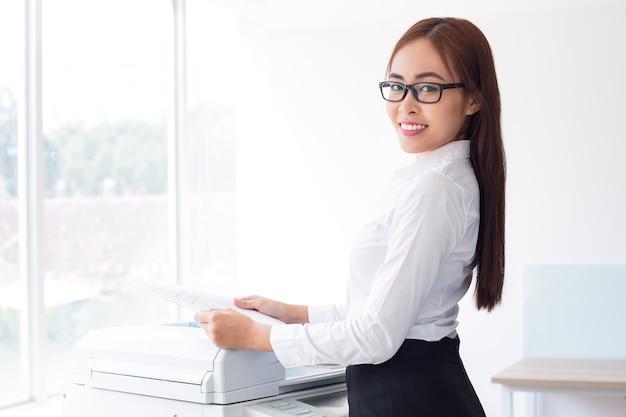Felice signora asiatica che per mezzo stampante multifunzione