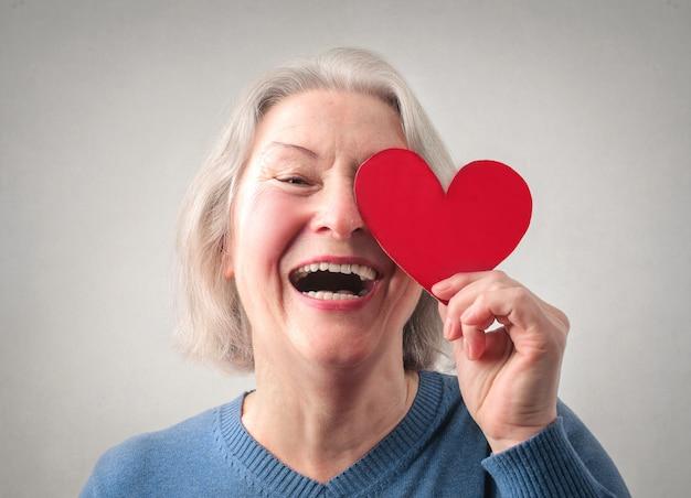 Felice signora senior con un cuore di carta