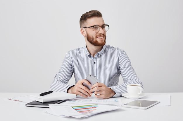 Felice sorridente barbuto giovane uomo d'affari guarda da parte come collega di avviso, si siede al posto di lavoro con un moderno telefono intelligente