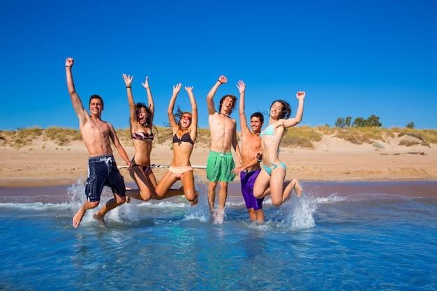 Felice spiaggia di ragazzi e ragazze adolescenti eccitati saltando